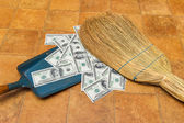 Money and broom — Stock Photo