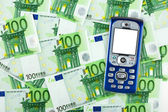 Mobile phone on money background — Stock Photo