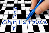 Hand filling in crossword - Merry Christmas — Stock Photo