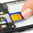 Hand install sim card to mobile phone — 图库照片