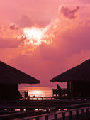 Human silhouette in water bungalow at sunset — Stock Photo