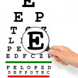 Stock Photo: Hand with magnifier and eyesight test chart