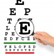 Hand with magnifier and eyesight test chart — Stock Photo