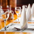 Glasses and plates on table in restaurant — Stockfoto