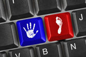 Printout of hand and foot on computer keys — Stock Photo