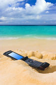 Mobile phone on sand beach — Stock Photo