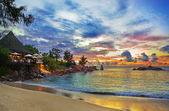 Cafe on tropical beach at sunset — Stok fotoğraf