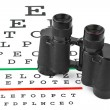 Binoculars on eyesight test chart — Stock Photo