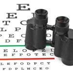 Binoculars on eyesight test chart — Stock Photo