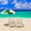 Chairs and umbrella at tropical beach - Stock Photo
