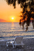 Chair on beach at sunset — Stock Photo
