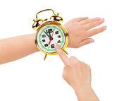 Handen en wekker zoals een horloge — Stockfoto