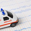 Toy ambulance car on ecg - Stock Photo