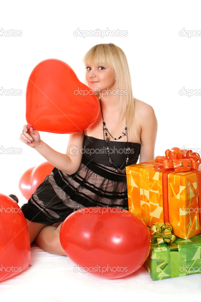 The young girl sits among gifts with a balloon in a hand in the form of heart  Stock Photo #2800512