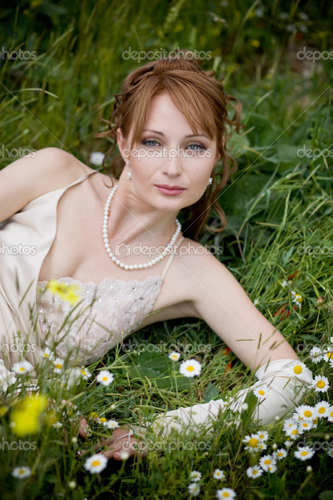 Bride relaxing in fresh grass with flowers — Stock Photo #2756088