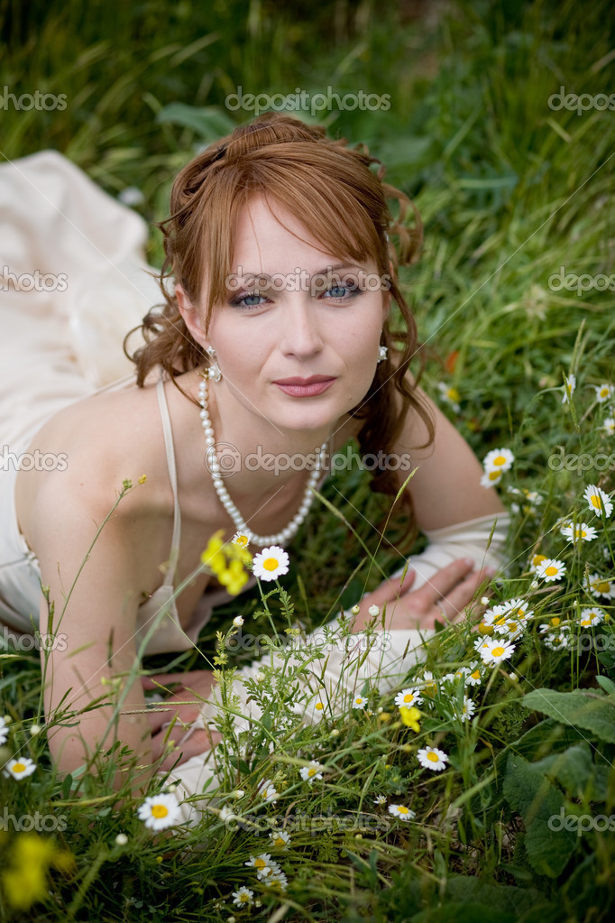 Bride relaxing in fresh grass with flowers — Stock Photo #2756103