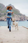 Girl with dog running — Stock Photo