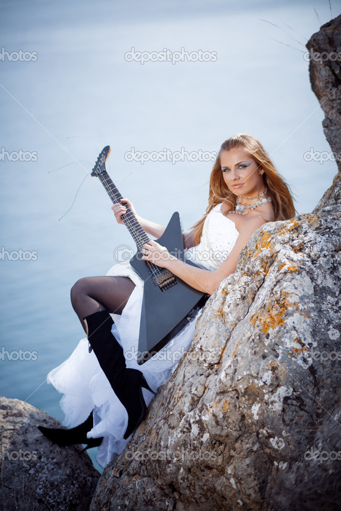 Beautiful creative bride posing with electrical guitar  Stock Photo #2766853