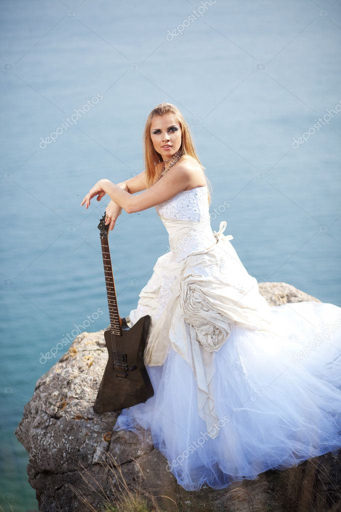 Beautiful creative bride posing with electrical guitar — Stock Photo #2766893