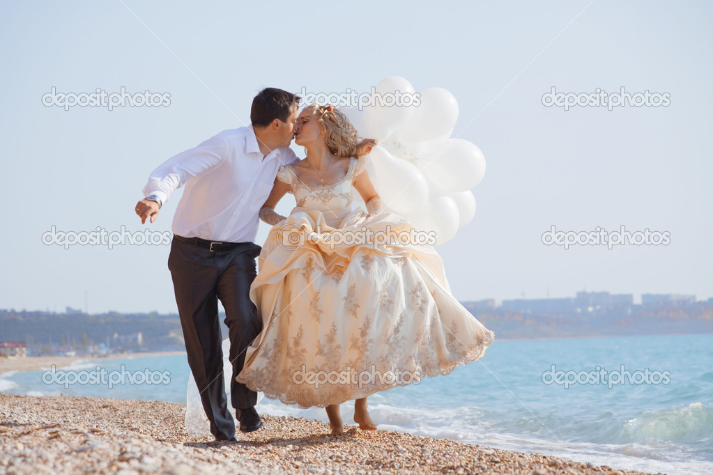 Wedding couple running and kissing on sea coast — Stock Photo #2768189