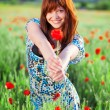 Smiling girl giving flower — Stockfoto