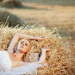 Bride resting in hay stack — Stock Photo