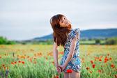 Smiling girl in poppy field — Stock Photo