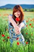 Smiling girl giving flower — Foto de Stock