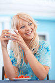 Smiling girl with cup of cappuccino — Stock Photo