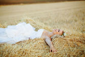 Bride in hay stack — Stock Photo