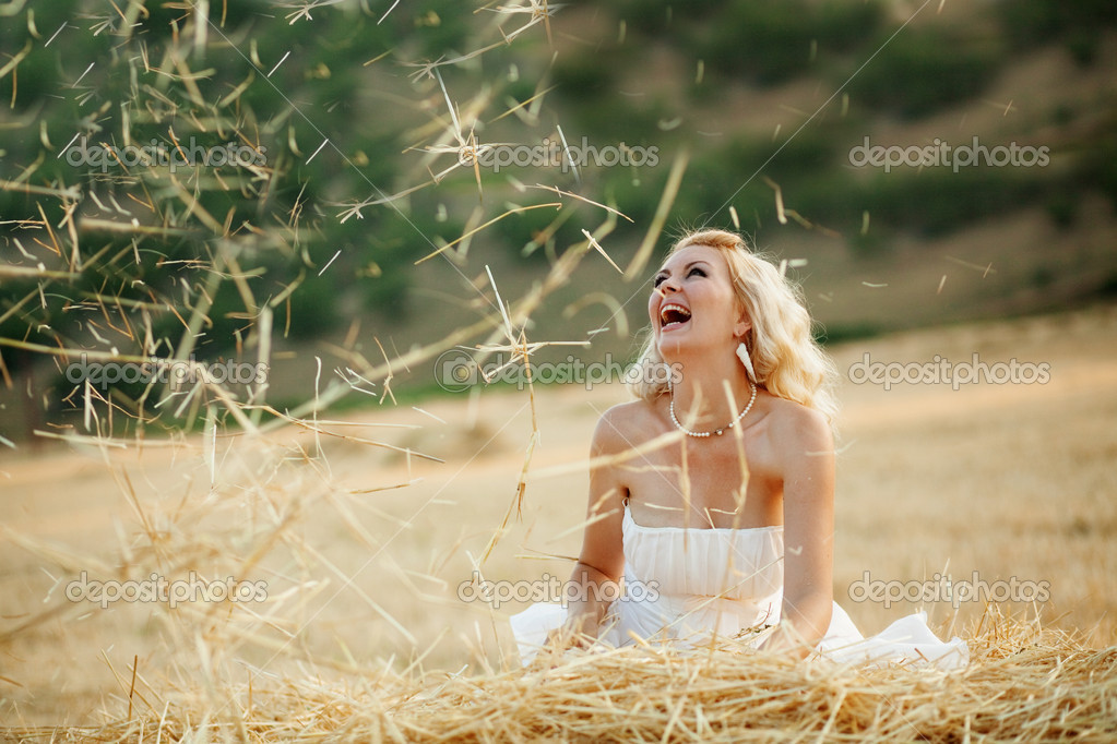 Happy bride playing with hey in field at her wedding day — Stock Photo #2772379