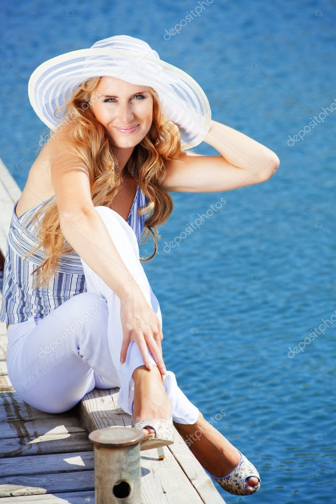 Beautiful young girl spend her vacation on berth near sea in summer day — Stock Photo #2773152