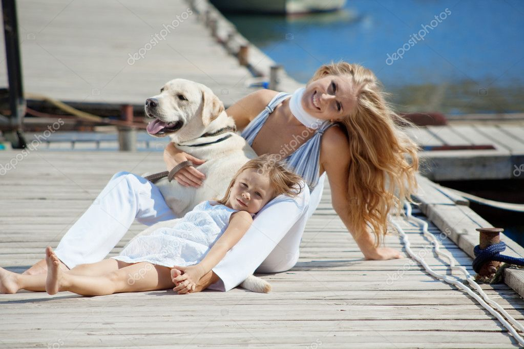 Happy family playing with dog on berth near sea in summer  Stock Photo #2773189