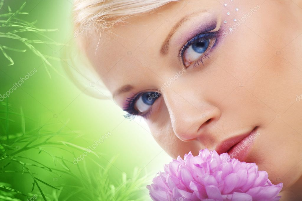 Cheerful young cute woman face with flower over natural green background — Stock Photo #2775789