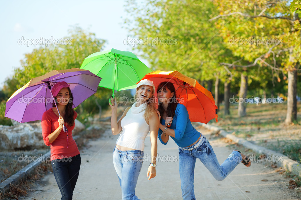 Three fashion teenage girls posing with colorful umbrellas in autumn park — Stock Photo #2776407