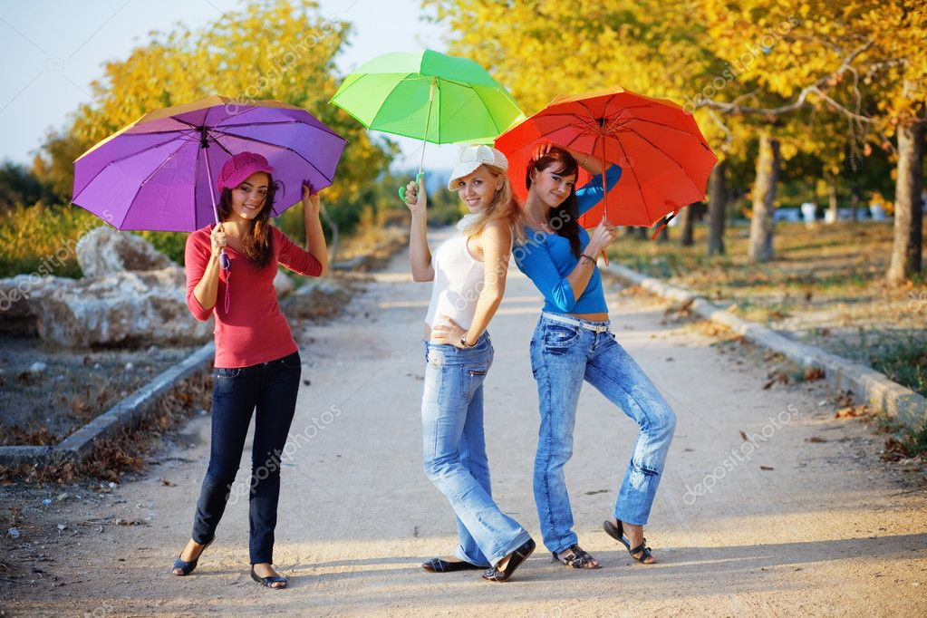 Three fashion teenage girls posing with colorful umbrellas in autumn park — Stock Photo #2776419
