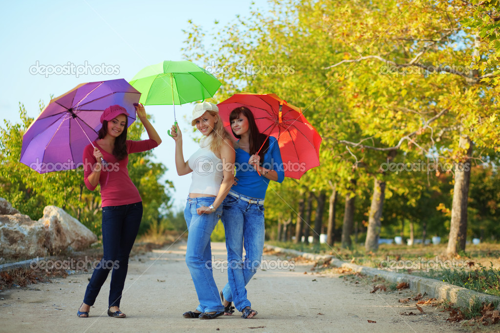 Three fashion teenage girls posing with colorful umbrellas in autumn park — Stock Photo #2776431