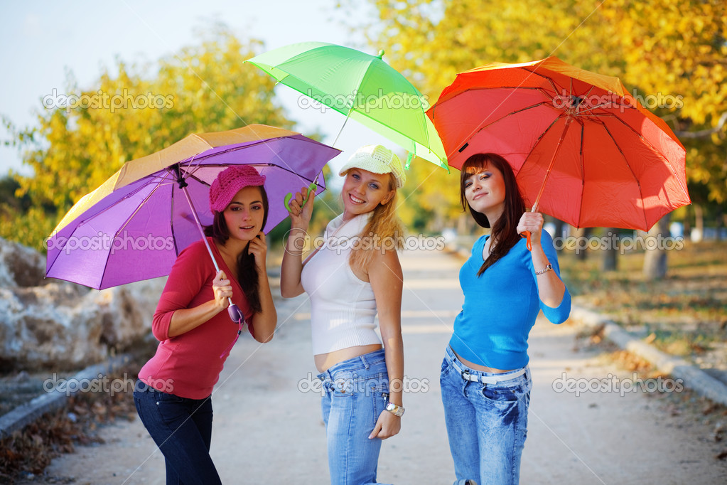 Three fashion teenage girls posing with colorful umbrellas in autumn park — Stock Photo #2776444