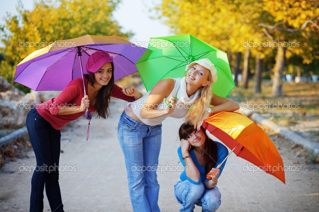 Three fashion teenage girls posing with colorful umbrellas in autumn park — Stock Photo #2776458