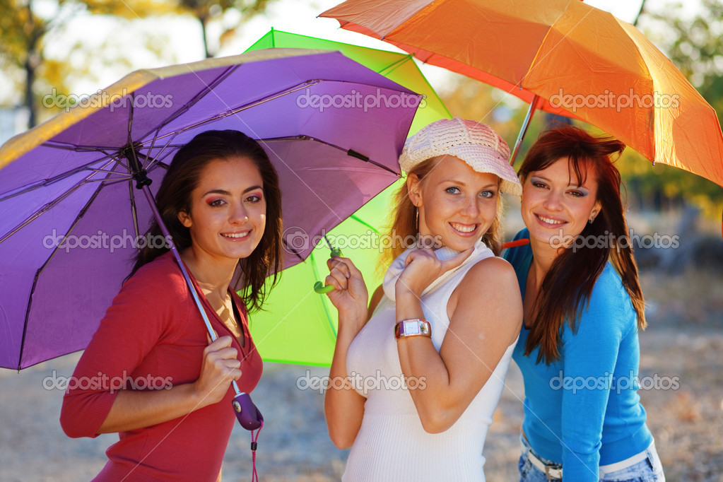 Three fashion teenage girls posing with colorful umbrellas in autumn park — Stok fotoğraf #2776584