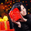 Stock Photo: Cute woman with presents at night