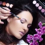 Make-up artist making eye visage to beautiful woman — Stock Photo #2784169