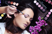 Make-up artist making eye visage to beautiful woman — Stock Photo