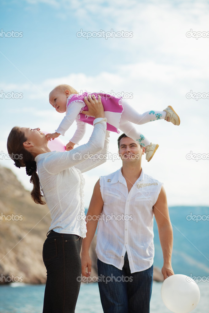 Portrait of happy young family playing with their child on berth near sea — Stock Photo #2780203