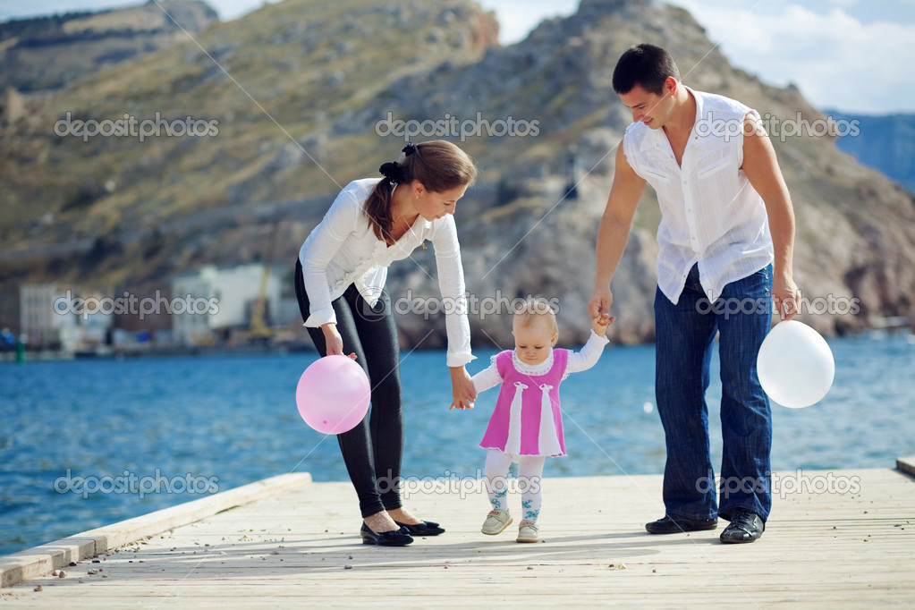 Portrait of happy young family walking with their child on berth near sea — Stock Photo #2780239