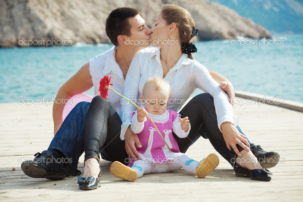 Portrait of loving young couple with their baby kissing on berth near sea  Stock Photo #2780261