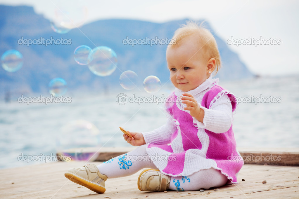 Portrait of little cute baby girl looking on soap bubbles on berth near sea — Stock Photo #2780361