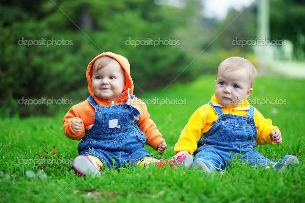 Cute twins babies sitting on fresh green grass in park  Stock Photo #2780477