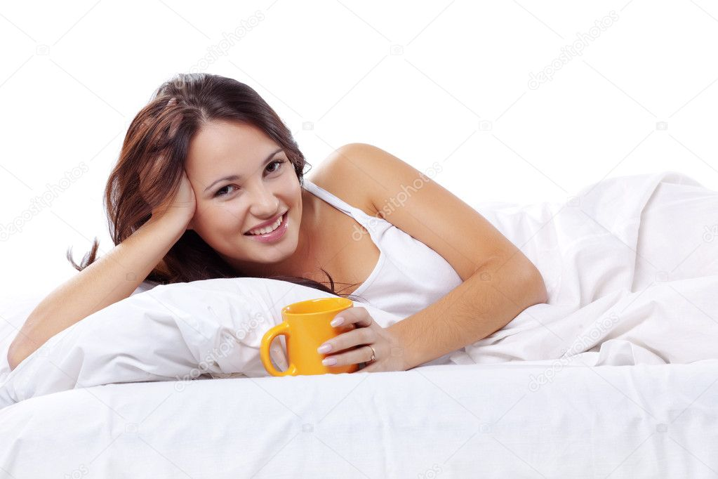 Studio portrait of young beautiful woman on bed — Stock Photo #2783323