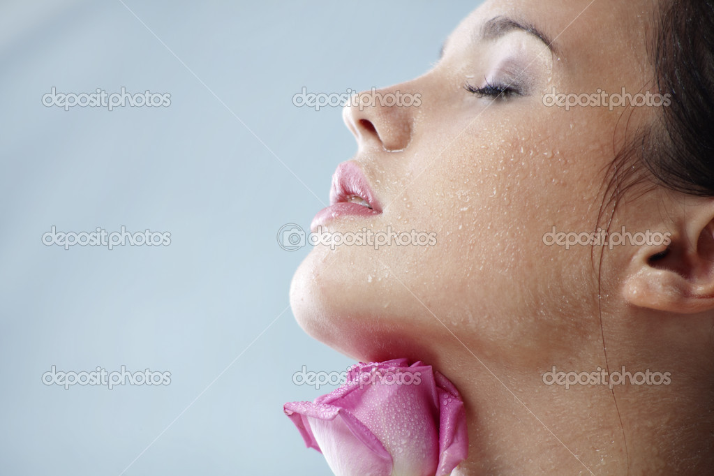 Studio portrait of sensual beautiful woman with rose and water droplets on her face — Stock Photo #2783586